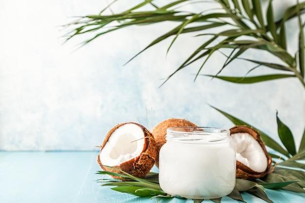 Kokosolie en kokosnoten op een lichte pastel achtergrond, selectieve aandacht.
