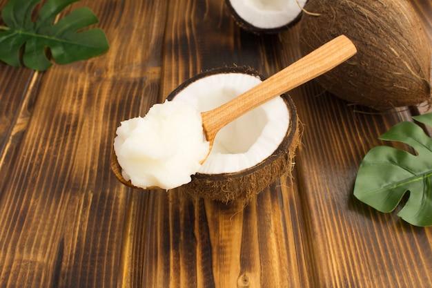 Kokosolie in de houten lepel in het midden van de bruine houten