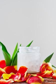 Kokosolie in een pot op wit omgeven door tulpenblaadjes, close-up met kopie ruimte