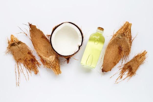 Kokosolie met kokosnoten op wit.