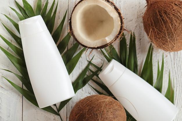 Kokosolie. zuivere natuurlijke kokosolie in witte flessen en verse kokosnoot in een snee met palmblad