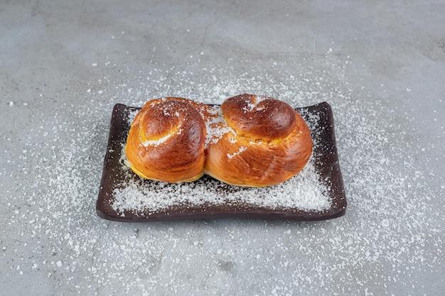 Kokospoeder bedekt schotel met zoete broodjes op marmeren tafel.