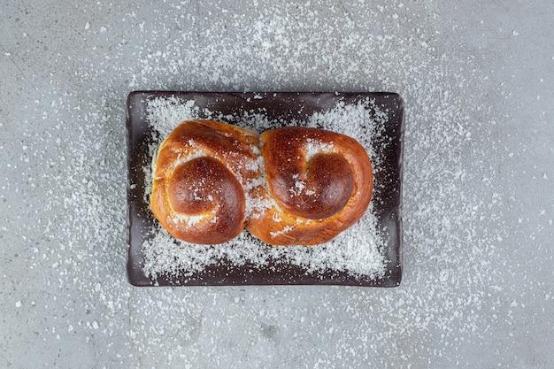 Kokospoeder verspreid op een broodje, een schotel en op een marmeren oppervlak