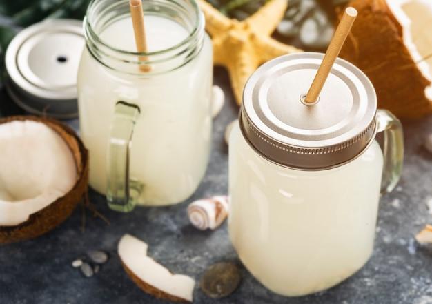 Kokossap of water of melk in glazen potten gezonde zomer tropische drank