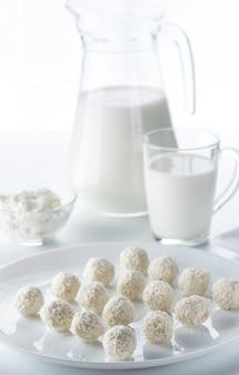 Kokossnoepjes op een achtergrond van een kan en een kopje melk en kommen kwark