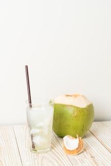 Kokoswater of kokossap in glas met ijsblokjes