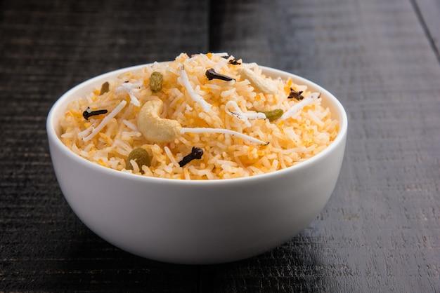 Kokoszoete rijstrecept ook bekend als narali bhat gemaakt met saffraan, cashewnoten, kruidnagel en geserveerd in een witte kom. populair konkani of maharashtriaans eten.