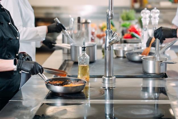 Koks bereiden maaltijden op een elektrisch fornuis in een professionele keuken in een restaurant
