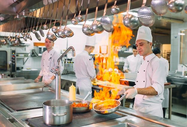 Koks bereiden maaltijden op het fornuis in de keuken van het restaurant of hotel.