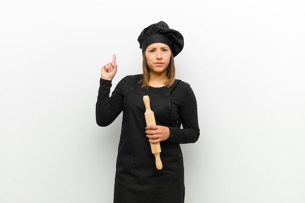 Kokvrouw die als een geniale holdingsvinger trots omhoog in de lucht voelen na het realiseren van een groot idee, zeggend eureka tegen witte achtergrond