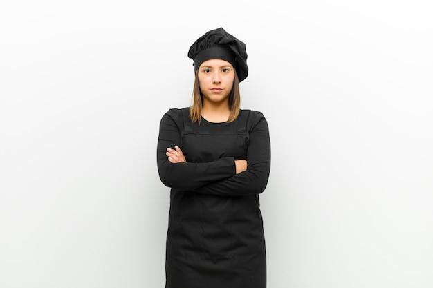 Kokvrouw die ontevreden en teleurgesteld voelen die ernstig geërgerd en boos met gekruiste armen kijken
