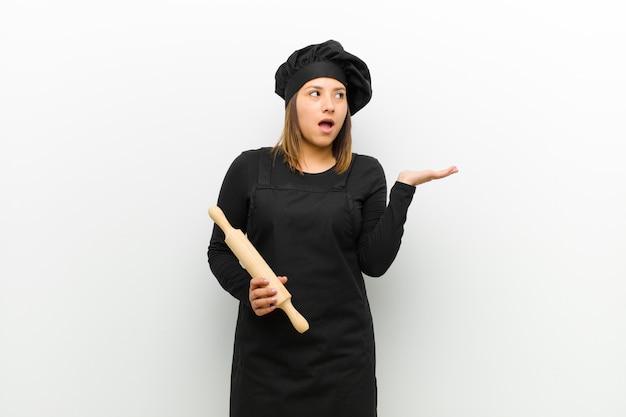 Kokvrouw die verrast en geschokt kijkt, met mond viel open met een voorwerp met een open hand aan de zijkant wit