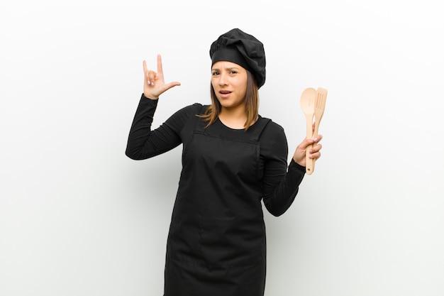 Kokvrouw die zich gelukkig, leuk, zelfverzekerd, positief en opstandig voelt, waardoor rock of heavy metal met hand tegen wit tekent