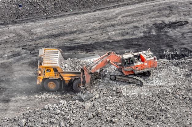 Kolenwinning in een steengroeve. een hydraulische graafmachine laadt een kiepwagen. laden van kolen in de carrosserie van een vrachtwagen.