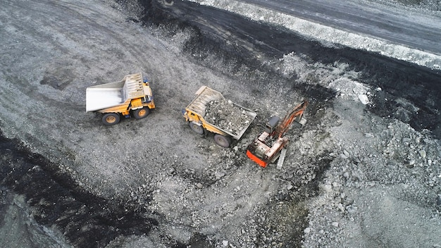 Kolenwinning in een steengroeve. een hydraulische graafmachine laadt een kiepwagen.