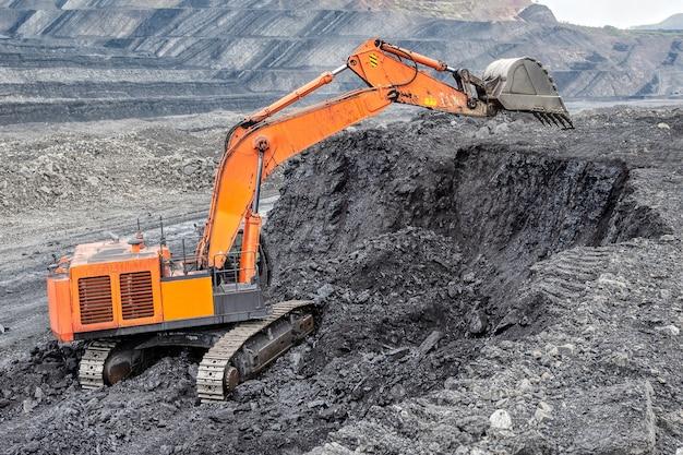 Kolenwinning met een hydraulische graafmachine. mijnbouw vanaf een verticaal vlak, een dagbouwmethode.