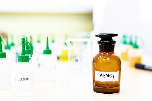 Kolf van de chemische industrie met vloeibare laboratoriumreageerbuizen staan op tafel in het laboratorium