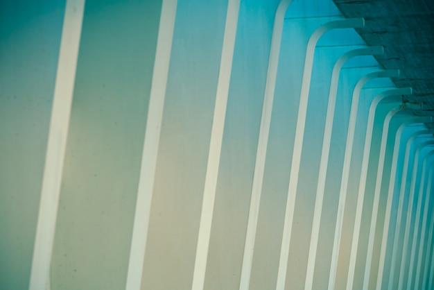 Kolommen van wit cement in een donkere scène, als achtergrond van moderniteit en architectuur.