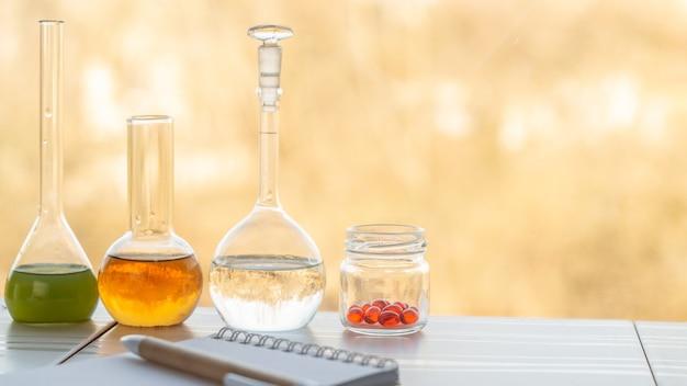 Kolven met reagentia, een potje met capsules met vitamines en een notitieboekje op tafel
