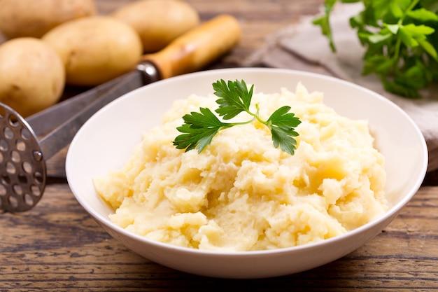 Kom aardappelpuree op houten tafel
