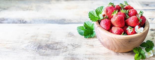 Kom aardbeien op een houten achtergrond. kopieer ruimte