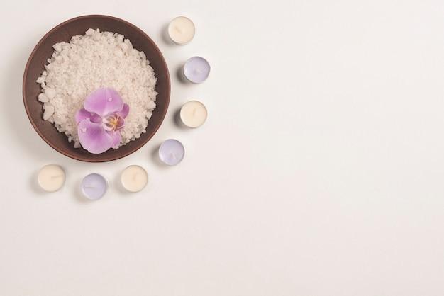 Kom badzout met orchideebloem die met kaarsen op witte achtergrond wordt verfraaid