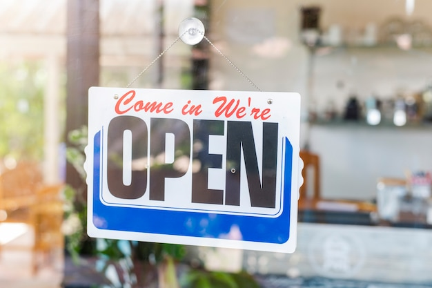 Kom binnen we zijn open bordbord op de toegangsdeur tot het zakenhotel, café, plaatselijke winkel, service-eigenaar die gasten verwelkomt na uitbraak van coronavirus Premium Foto