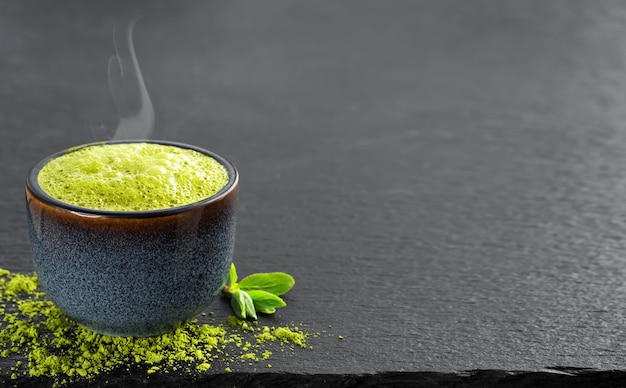 Kom blauw met matcha groene thee, daarnaast staan theeblaadjes en theepoeder op tafel