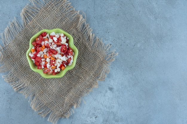 Kom bloemkool en pepersalade op marmer.
