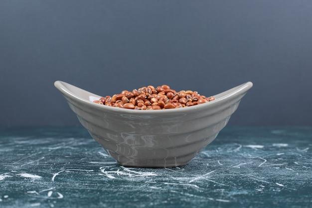 Kom bruine bonen op blauwe achtergrond. hoge kwaliteit foto