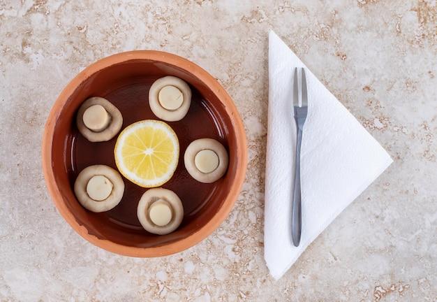 Kom champignons en een schijfje citroen naast een kleine vork op marmeren oppervlak.