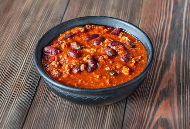 Kom chili con carne op een houten tafel