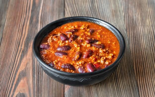 Kom chili met vlees op een houten tafel