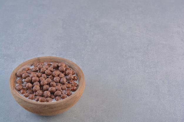 Kom chocolade granen ballen met melk op stenen achtergrond.