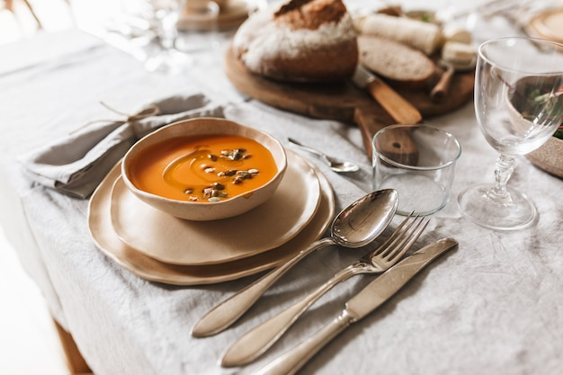 Kom crème pompoensoep en vers brood op houten bord op lunch in gezellig café close-up