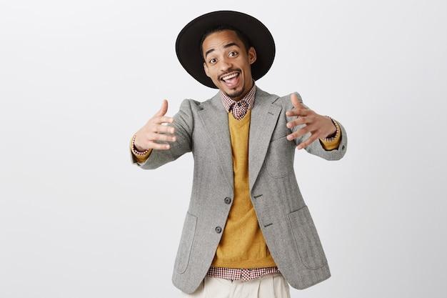 Kom dichterbij, laat me je knuffelen. positieve vriendelijke afro-amerikaanse man in trendy outfit en hoed trekken handen naar
