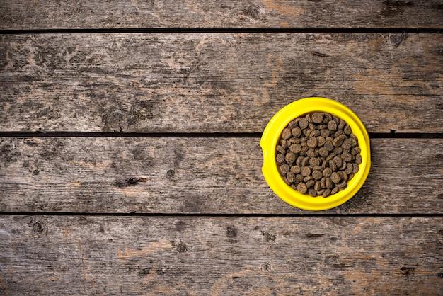 Kom droog hondenvoedsel op houten vloer