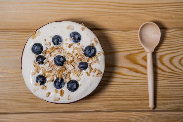 Kom eigengemaakte granola met yoghurt en verse bessen op houten achtergrond