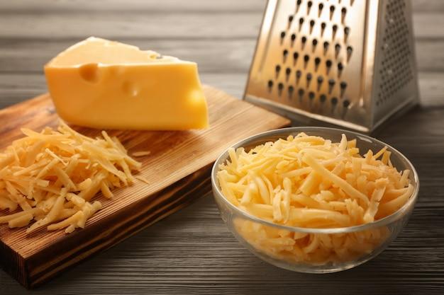 Kom en houten plank met geraspte kaas op tafel