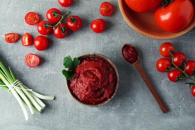 Kom en lepel met tomatenpuree op grijze ondergrond met ingrediënten