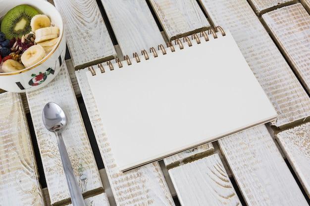 Kom fruitsalade met lepel en leeg spiraalvormig notitieboekje op houten geweven achtergrond