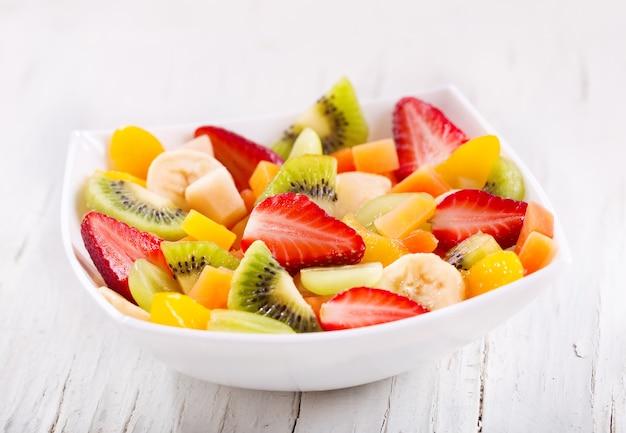 Kom fruitsalade op een houten tafel