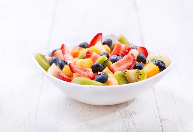 Kom fruitsalade op houten tafel