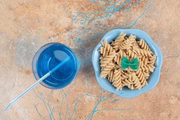 Kom fusilli pasta en glas blauwe cocktail op marmeren ruimte.