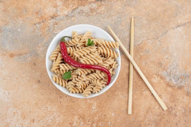 Kom fusilli pasta met peper en eetstokjes op marmeren tafel. hoge kwaliteit foto
