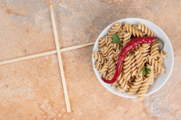 Kom fusilli pasta met peper en eetstokjes op marmeren tafel