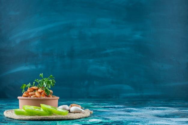 Kom gebakken bonen, knoflook en peper op een onderzetter, op de blauwe tafel.