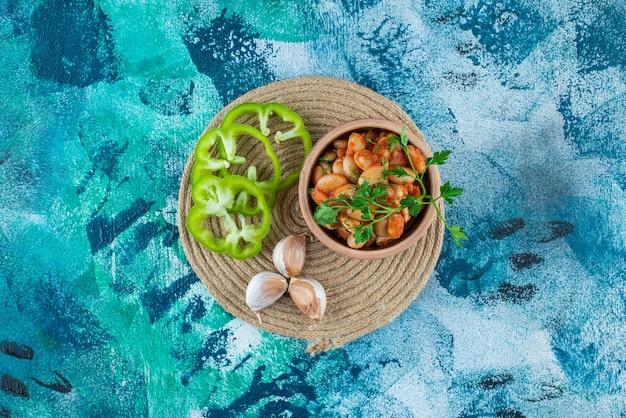 Kom gebakken bonen met peterselie naast knoflook een peper op een onderzetter, op de blauwe tafel.