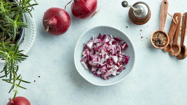 Kom gehakte rode uien op lichtblauwe keukentafel bovenaanzicht