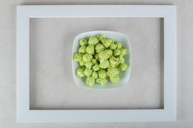 Kom gekonfijte popcorn in het midden van een leeg frame op marmer.